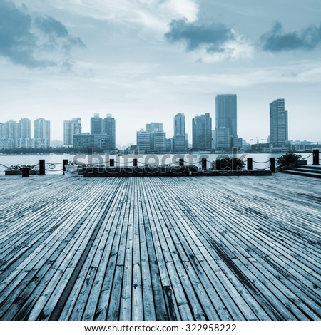 wooden platform before modern city - stock photo
