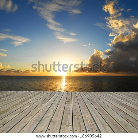 Wooden platform beside tropical sea with sunrise - stock photo