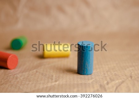 Wooden playing pieces (colors) on brown background