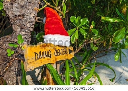 Wooden pointer to the diving center with cristmas hat on the  island Biyadhoo, Maldives, The Indian Ocean