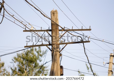 wooden pole and tangled cables - stock photo