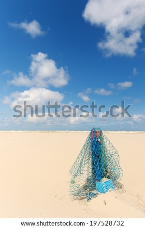 Wooden pole with fishing net at the beach of Dutch wadden island Terschelling - stock photo