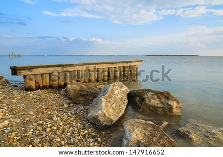 Wooden poles and  stones on Neusiedler See lake in afternoon light, Burgenland, Austria - stock photo
