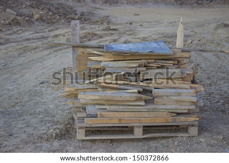 wooden poles on a pallet, used at the construction site - stock photo