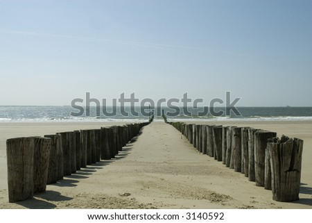 wooden poles on the beach to break the waves - stock photo