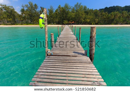 Wooden pontoon in the turquoise tropical sea of Ao Phrao beach in Ko Mook island, Thailand .