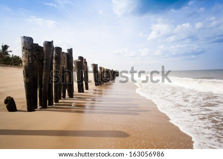 Wooden posts on the beach, Pondicherry, India - stock photo