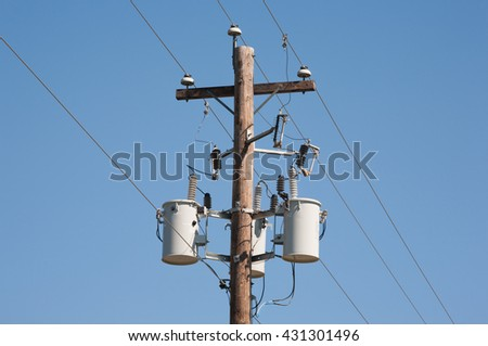Wooden power utility pole and clear blue sky. - stock photo
