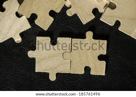 Wooden puzzle on black background. Close up