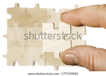 Wooden puzzle on white background. Hand holding puzzle piece. White isolated