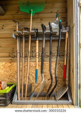 Wooden rack with different garden tools and equipment - stock photo
