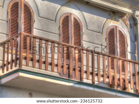 wooden railing in an old balcony. Processed for hdr tone mapping effect. - stock photo