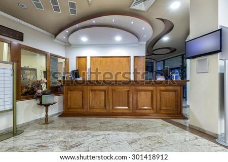Wooden reception desk - reception area in hotel - stock photo