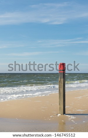 Wooden red beach pole at the coast of the Northsea - stock photo
