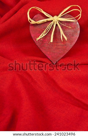 Wooden red heart on red cloth as a symbol of love - stock photo