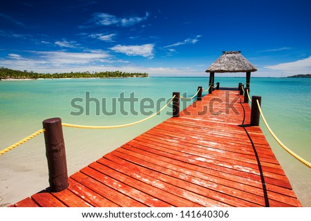 Wooden red jetty extending to tropical green lagoon - stock photo