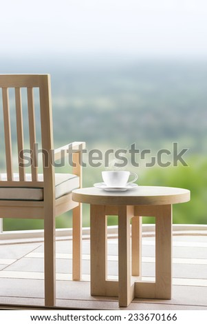 Wooden relax chairs and coffee cup with country view background.