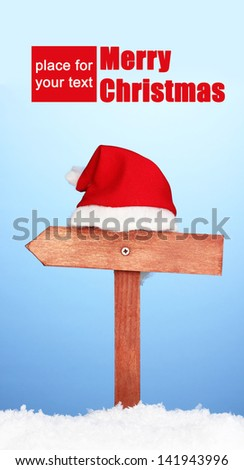 Wooden road sign with Santa hat on blue background - stock photo