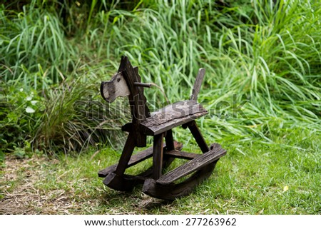 Wooden rocking toy on yard garden.