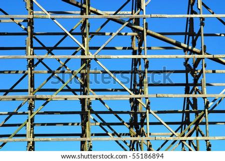 wooden roller coaster framework against blue sky - stock photo