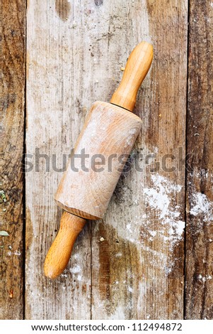 Wooden rolling pin with remnants of flour in a rustic kitchen on an old grainy textured wood surface - stock photo
