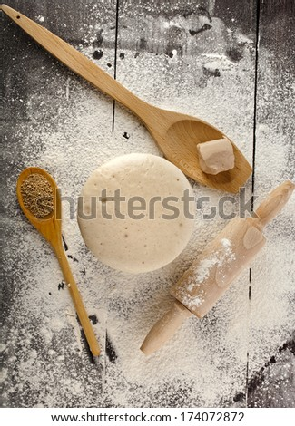 Wooden rolling pin with white wheat flour  on the black surface table.. top view - stock photo