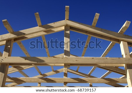 Wooden roof during the early stages of construction in a sunny day - stock photo
