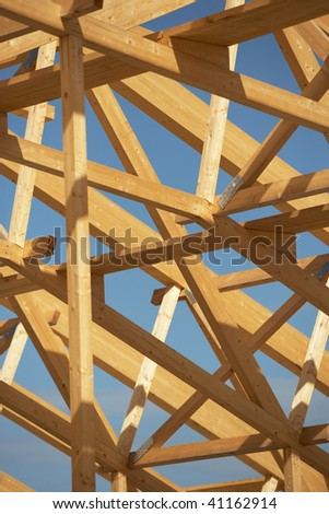 Wooden roof frame on a constructon site over blue sky with clouds. - stock photo