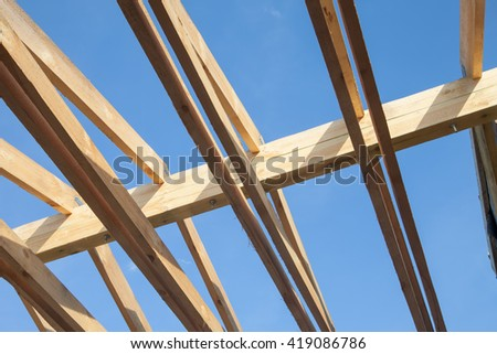 Wooden roof with rafter style framing against a blue sky - stock photo