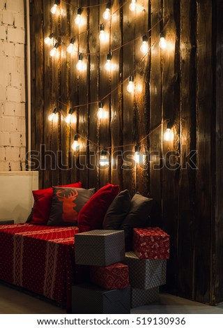 Wooden room in rustic house with wall and designer light bulbs, decorated place for seat. Red gray pillows.
