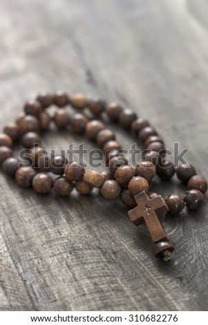 Wooden rosary beads on old wooden background, close up - stock photo