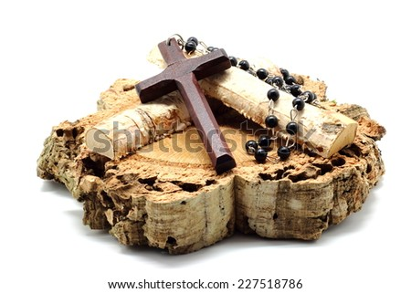 Wooden rosary on a log isolated on white background - stock photo