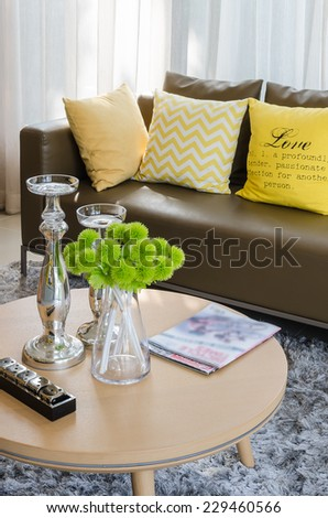 wooden round table with brown sofa in living room at home - stock photo