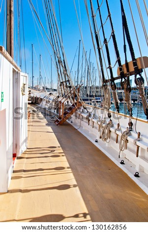 Wooden sailboat deck, masting and rigging - stock photo