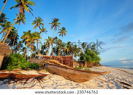 Wooden sailboat  (dhow) and palm trees on a tropical beach of Zanzibar island - stock photo