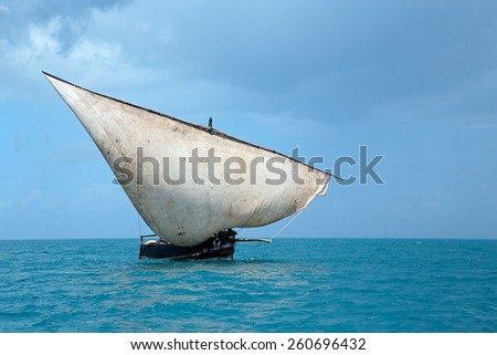 Wooden sailboat (dhow) on water with clouds, Zanzibar island - stock photo