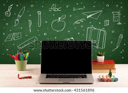 Wooden school desk with stuff and blackboard full of drawings concept - stock photo