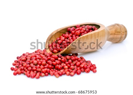 Wooden scoop filled with dried pink pepper berries, isolated.