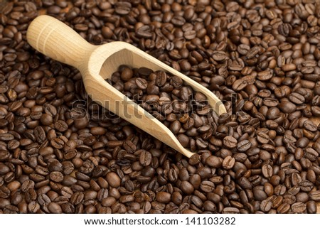 wooden scoop in a coffee beans background - stock photo