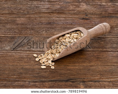 Wooden scoop portion of organic, whole grain oats. With copy space.