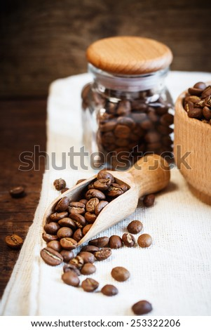 Wooden scoop with coffee beans on burlap sack  - stock photo