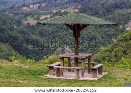 Wooden seating bench with table in nature under wooden umbrella, makes a good resting place. - stock photo