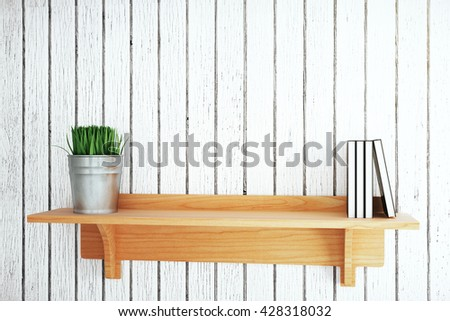 Wooden shelf with plant and books on grey plank background. Mock up, 3D Rendering
