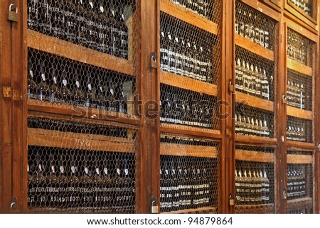 Wooden shelves with bottles of wine. Storage space for an expensive aged wines - Madeira. - stock photo