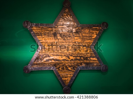 Wooden Sheriff Star on green wall - stock photo