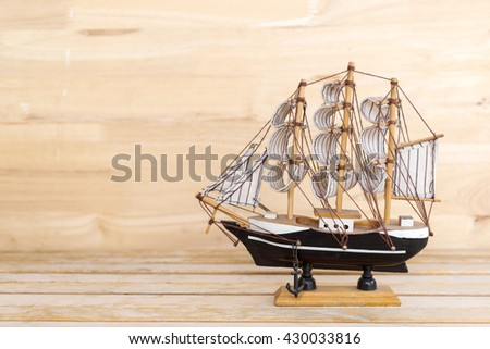 wooden ship model on the table at wood wall background - stock photo