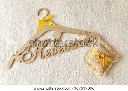 "Wooden shoulder with inscription ""Bride"" in Russian language. Wedding rings. Wedding morning and preparation. clothes hanger"