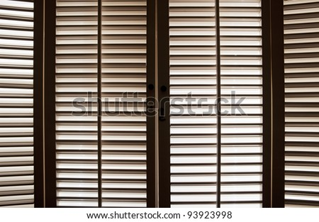 Wooden shutters in front of bright, sunlit windows - stock photo