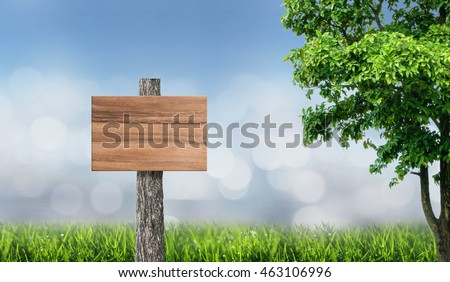 Wooden sign board background in green meadow with blurred background and bokeh of light.