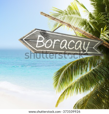 Wooden sign Boracay on tropical white sand beach summer background. Lush tropical foliage and sunshine. Blue ocean at perfect day. No people. - stock photo